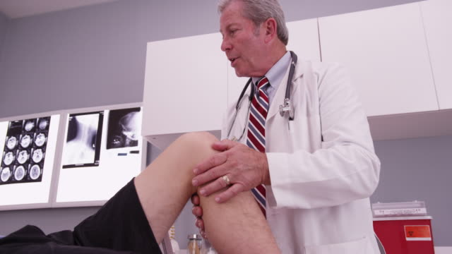 male caucasian patient having knee examined by mid aged doctor - knee stock videos & royalty-free footage
