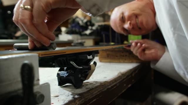 vídeos de stock, filmes e b-roll de um técnico de esqui caucasiano masculino na casa dos 50 verifica o nível básico de flatness de um esqui em uma oficina interior - equipamento esportivo