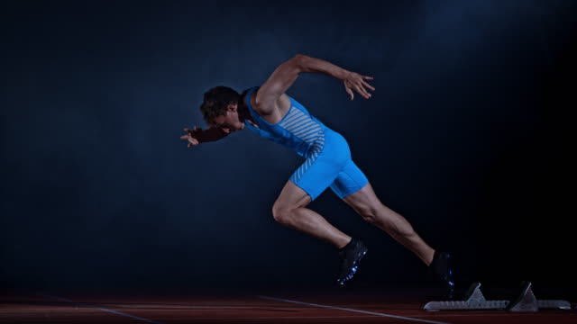 SLO MO TS Male Caucasian sprinter starting and running on a black misty background