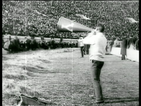 B/W 1905 male cheerleader with megaphone on field at Harvard vs Yale football game / newsreel