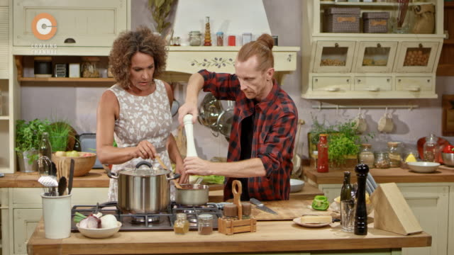 Male chef and his female guest cooking on a live cooking show