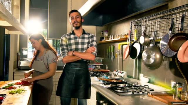 männlicher koch kochen und lächeln auf die kamera - cooker stock-videos und b-roll-filmmaterial