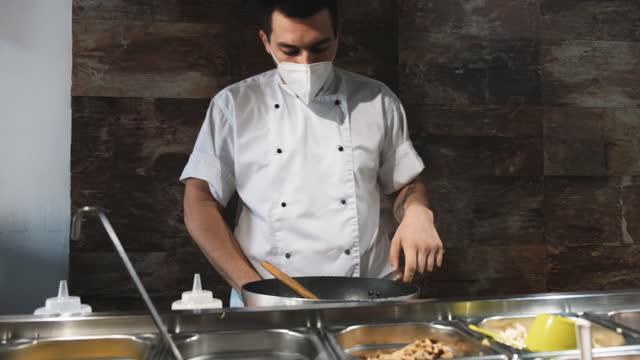 covid-19のファーストフードレストランで調理する男性シェフ - フライパン点の映像素材/bロール