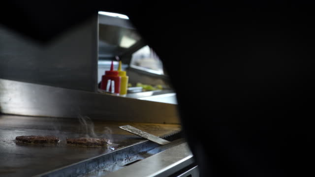 stockvideo's en b-roll-footage met male chef grilling and flipping hamburger patties - burger menselijke rol