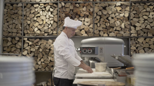 Male chef preparing a pizza and kneading the dough