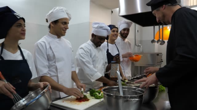 male chef teaching his students about the different ingredients and encouraging them to smell them - food and drink stock videos & royalty-free footage