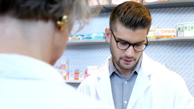 männliche chemiker, die unterstützung von älteren kunden im store - apothekerberuf stock-videos und b-roll-filmmaterial