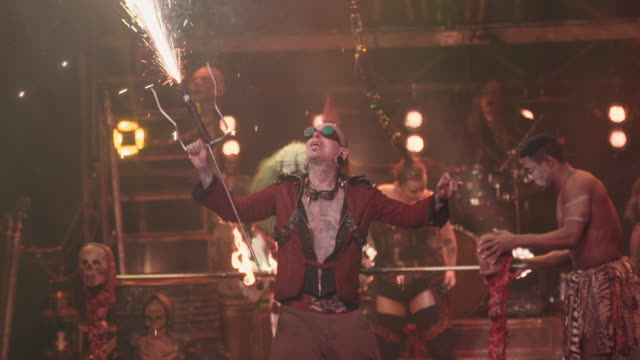 vidéos et rushes de a male circus performer in steampunk attire fires pyro into the air during a circus show filmed in slow motion - théâtre burlesque