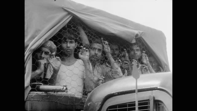 male civilians are rounded up by soldiers as women and children watch helplessly as they drive away - westbengalen stock-videos und b-roll-filmmaterial