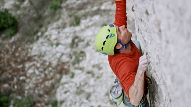 vídeos de stock e filmes b-roll de male climber ascending the cliff with aa green helmet on his head - esforço