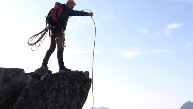 male climber ascends to mountain summit - one mature man only stock videos & royalty-free footage