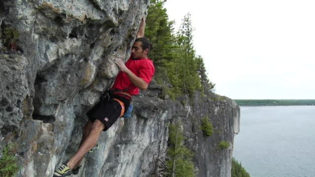 SLO MO WS PAN Male climber climbing cliff, Lion's Head, Ontario, Canada
