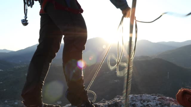 stockvideo's en b-roll-footage met male climber coils rope at cliff edge - alleen oudere mannen