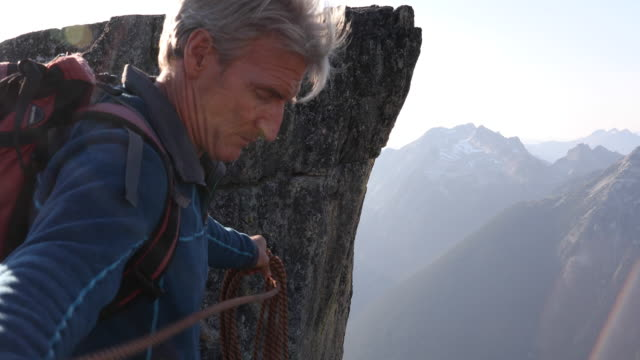 male climber coils rope on mountain summit - three quarter length stock videos & royalty-free footage