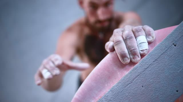 vídeos y material grabado en eventos de stock de slo mo escalador masculino que encuentra un agarre en una pared en un gimnasio de escalada interior - escalada libre