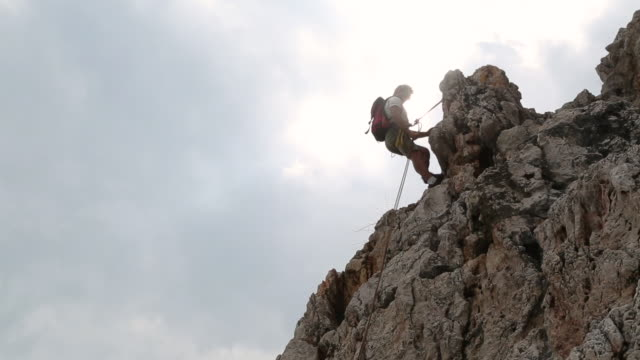 male climber rappels (abseils) from anchor - abseiling stock videos & royalty-free footage
