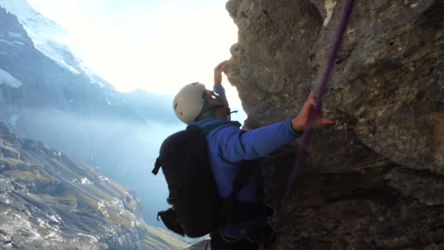 Male climber reaches edge of cliff face above glaciated mountains