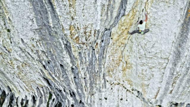 vídeos de stock e filmes b-roll de aerial male climber securing himself while climbing up a cliff - dedicação