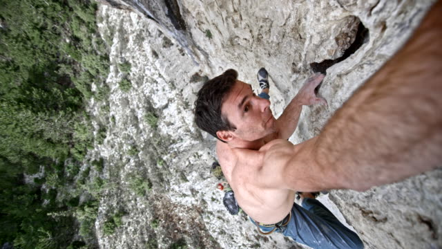 slo mo male climber stretching his hand to find a grip in the cliff - rischio video stock e b–roll