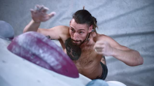 vídeos y material grabado en eventos de stock de slo mo ld escalador masculino tratando de atrapar una bodega en un gimnasio de boulder interior, pero dejando ir - escalada libre