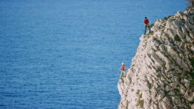 彼女は海の上のギザギザの崖の頂上に登り、彼の女性のパートナーを待っている LD 男性登山者