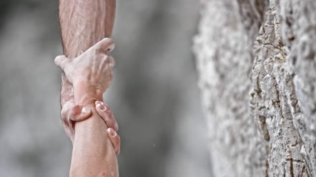 vidéos et rushes de main de l'alpiniste slo mo ld mâle saisissant la main de l'alpiniste femelle - force