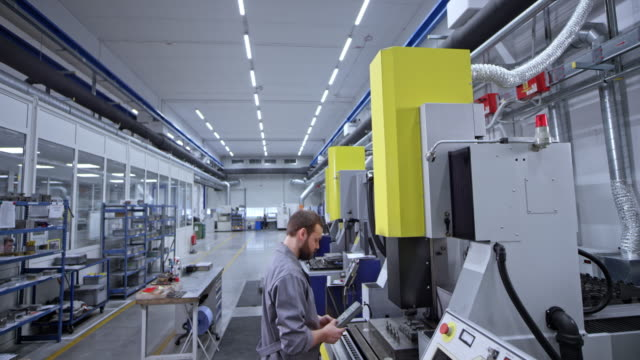 vidéos et rushes de cs male opérateur de machine cnc actionne la machine dans l'usine - machinerie