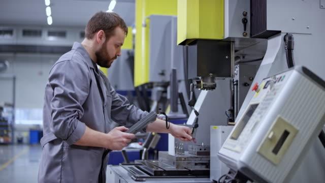 stockvideo's en b-roll-footage met ds male cnc operator met behulp van een controller om een machine te bedienen - machinerie