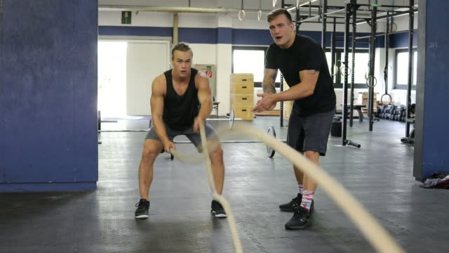 vídeos de stock, filmes e b-roll de treinador masculino homem exercitar com cordas a bater palmas - instrutor de fitness
