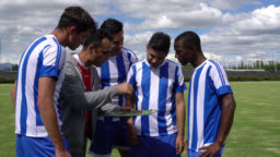 Male coach talking about game strategies to his diverse team before starting a soccer match