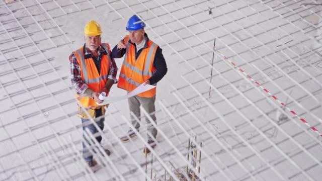 vídeos de stock, filmes e b-roll de coordenador e encarregado de construção masculinos do ld que prendem as plantas no edifício industrial a construção e a fala - engenheiro