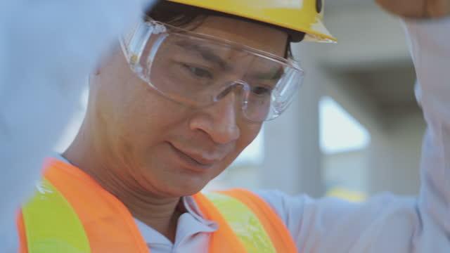 vidéos et rushes de gestionnaire masculin de construction - lunettes de protection