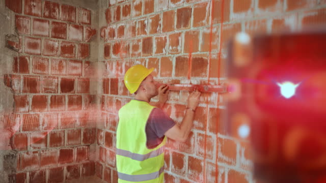male construction worker drawing horizontal lines on the wall of the building with the help of a laser measurer - brick stock videos & royalty-free footage