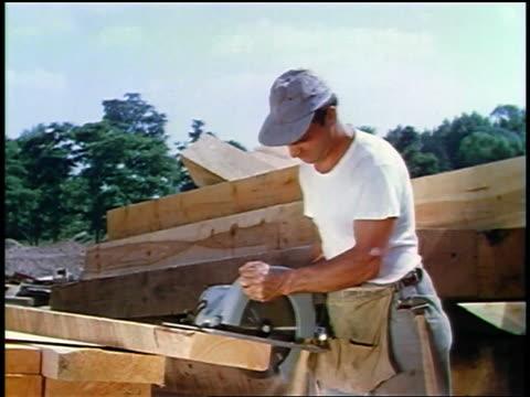 vídeos de stock, filmes e b-roll de 1957 male construction worker in hat cutting wood with power saw - serra elétrica
