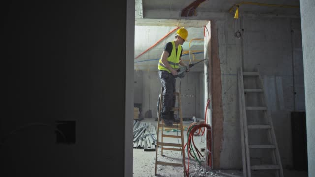 ld male construction worker making a hole in the wall inside a building under construction - electrician stock videos & royalty-free footage