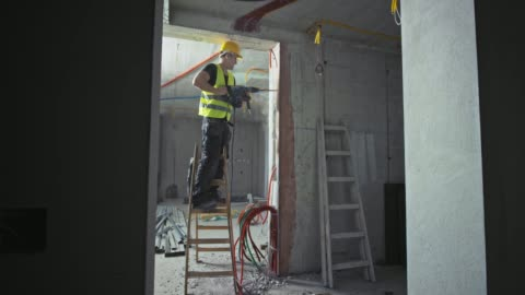 ds male construction worker using a jackhammer while standing on the ladder inside a building - construction site stock videos & royalty-free footage