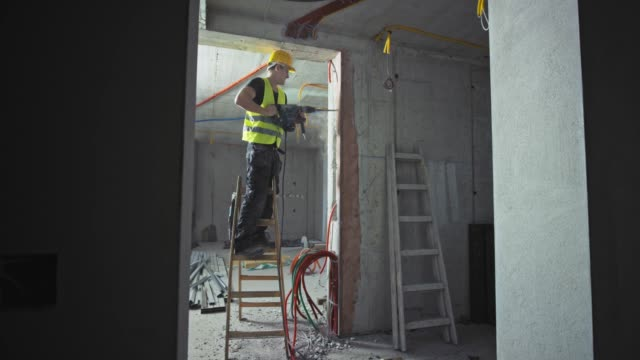 ds male construction worker using a jackhammer while standing on the ladder inside a building - construction equipment stock videos & royalty-free footage