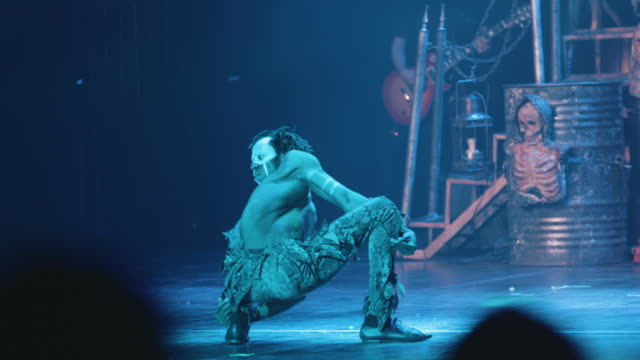 vidéos et rushes de a male contortionist adorned in face paint twists and distorts his body during a circus performance - théâtre burlesque