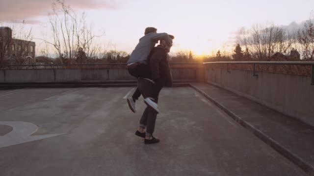 male couple piggy backing on top of a parking structure - bisexuality stock videos and b-roll footage