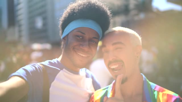 male couple taking a selfie during lgbtqi parade - gay pride stock videos & royalty-free footage