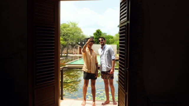 MS Male couple taking selfie on balcony of room overlooking courtyard of luxury tropical resort