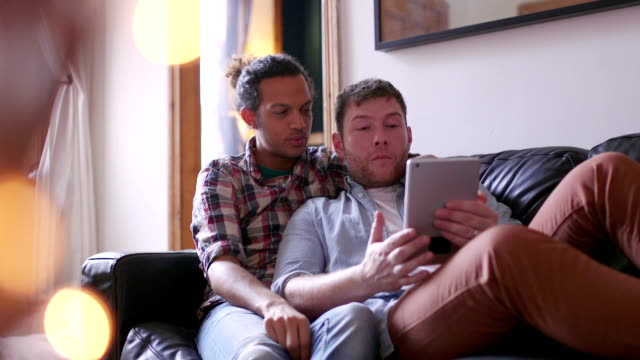 male couple using digital tablet - home shopping stock videos & royalty-free footage