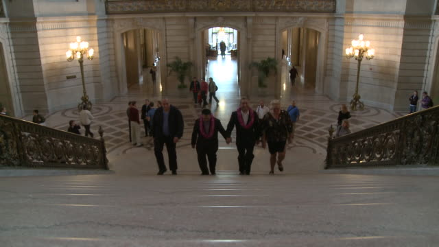 Male couple wearing leis walking up steps with friends to get married at San Francisco City Hall/ San Francisco California/ AUDIO
