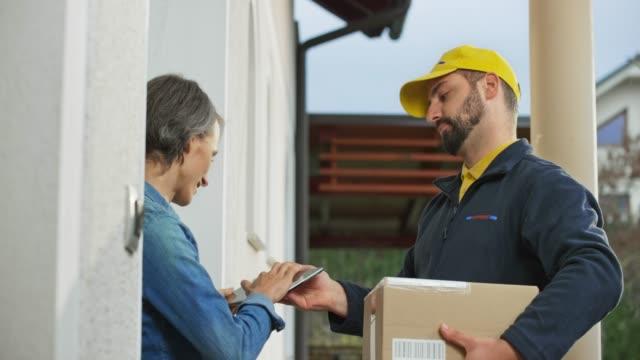 女性に小包を届ける男性宅配便 - 受ける点の映像素材/bロール