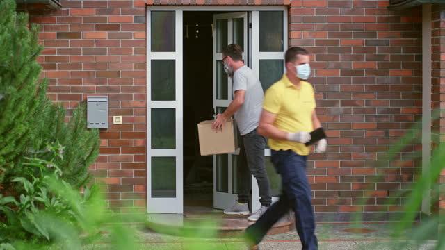 vidéos et rushes de courrier masculin livrant un colis sans contact physique pendant la pandémie de coronavirus - paquet