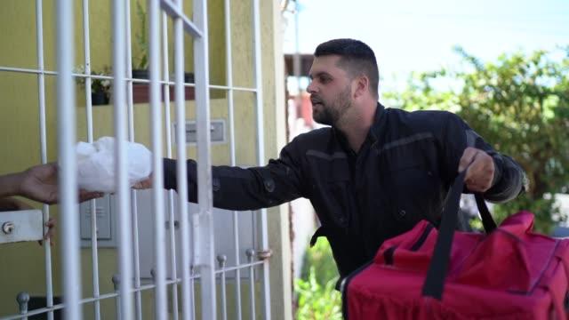 vídeos de stock, filmes e b-roll de mensageiro masculino entregando comida para um casal na porta da frente - receber