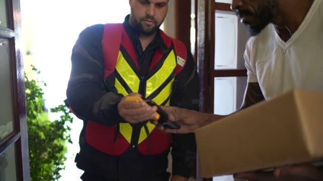 vídeos de stock, filmes e b-roll de mensageiro masculino entregando pacotes para um homem e o seu está pagando por isso - receber