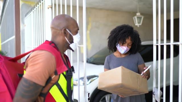 vídeos de stock, filmes e b-roll de mensageiro masculino entregando pacotes para mulher em sua porta da frente - com máscara facial - carteiro