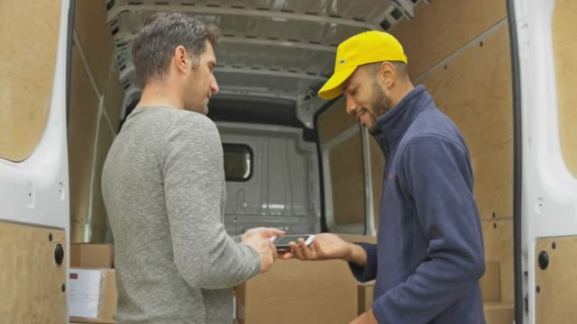 male courier giving the male customer a pod to sign before handing him the package - van vehicle stock videos & royalty-free footage