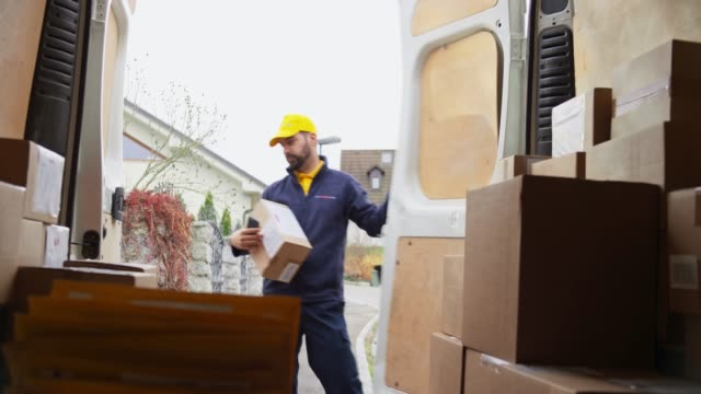 male courier scanning a package and walking out of the van - commercial land vehicle stock videos & royalty-free footage